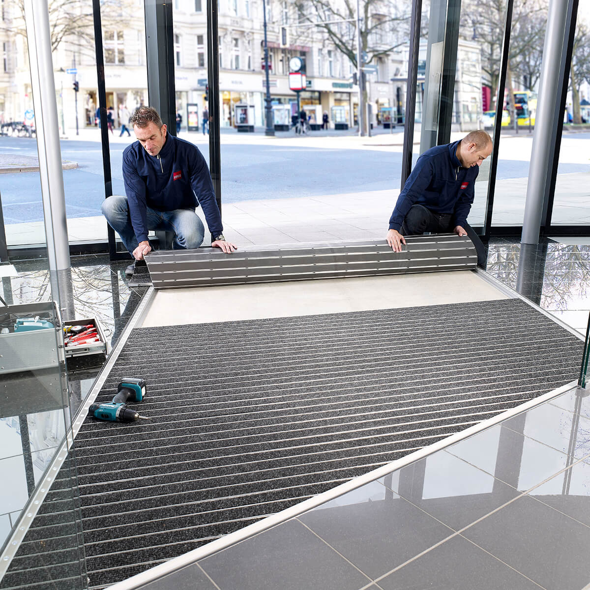 Service team install entrance mat